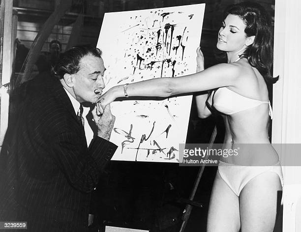 Spanish artist Salvador Dali kisses American actor Raquel Welch's hand in front of his abstract portrait of her Welch is wearing a bikini