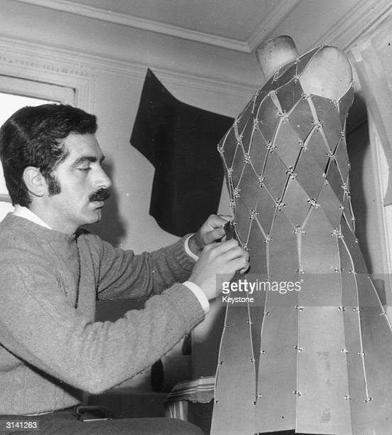 Spanish born dress designer Paco Rabanne at work on one of his metallic dresses.
