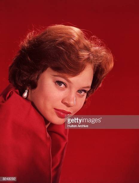 Studio headshot of Indianborn actor Juliet Prowse wearing a red top red lipstick and pearl earrings 1960s