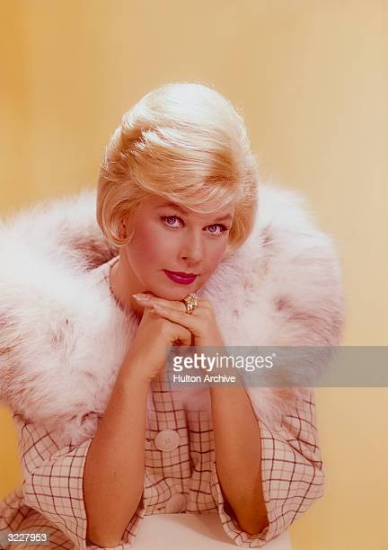 Studio headshot portrait of American actor and singer Doris Day resting her chin on her hands and wearing a brownandtan striped jacket with a large...