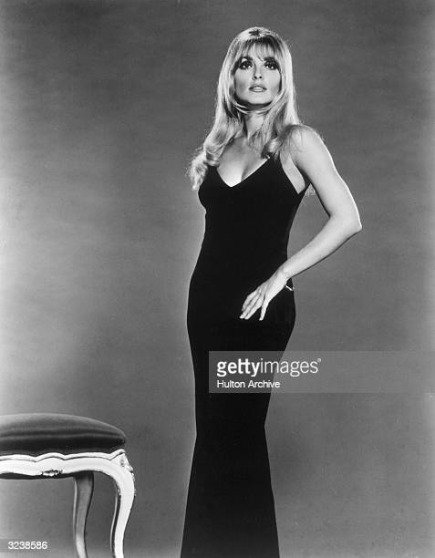 Studio portait of American actor Sharon Tate posing in a black grown with her hand on her hip.