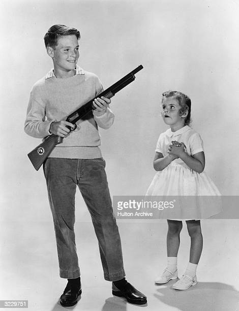 Studio portrait of a boy holding a Dick Tracy toy rifle as a little girl in a dress looks on admiringly 1960s