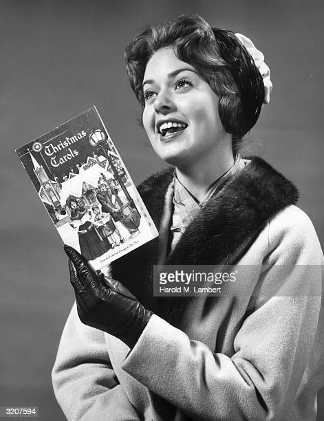 Studio portrait of a woman singing Christmas carols from a holiday song book 1960s She wears a winter coat and leather gloves