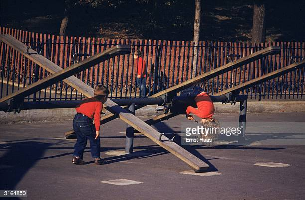 Two children playing among the seesaws in a playground