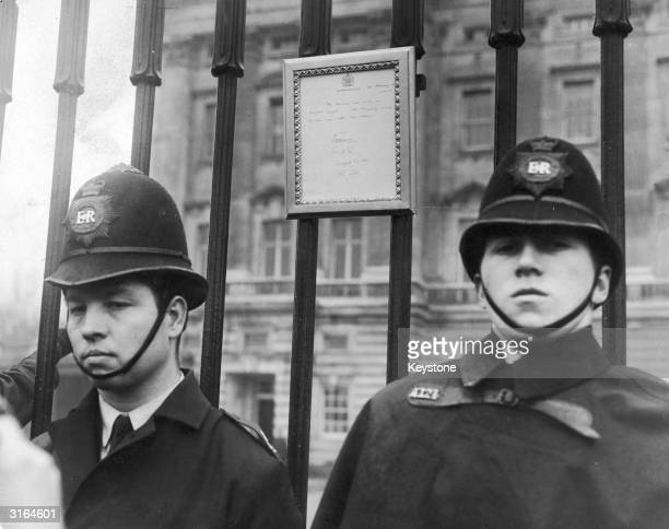 Two policeman standing either side of a royal bulletin announcing the birth of the Queen's new son Edward at Buckingham Palace London