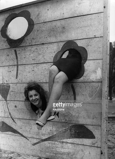 Two young women pose behind a wall with holes in it the photograph giving the impression that there is a single woman whose head is separated from...