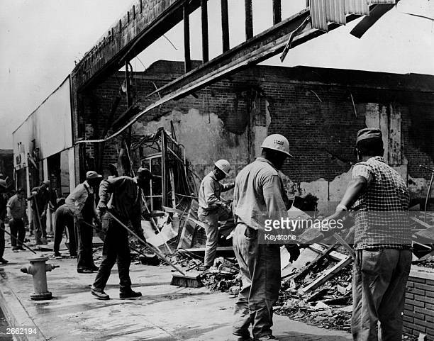 Workmen sweeping up debris left by the Los Angeles Watts riots on 103rd Street