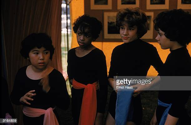 Young girls in black leotards worn with coloured sashes