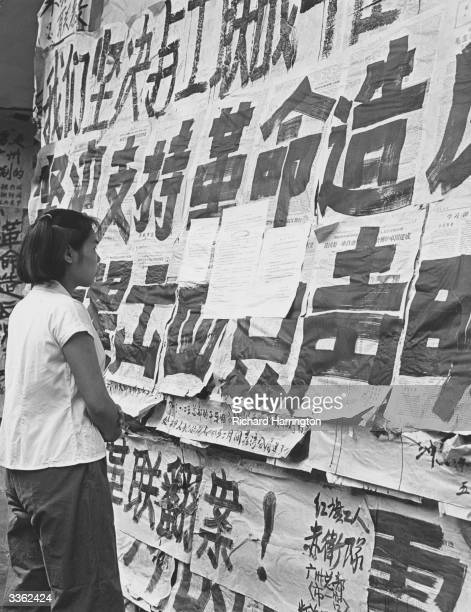 A Chinese girl reading dazebao which completely cover the windows of a department store at Canton during the Cultural Revolution Some are government...