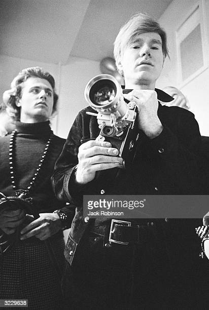 American pop artist Andy Warhol holds a camera fitted with a zoom lens while standing with photographer poet and archivist Gerard Malanga at club...
