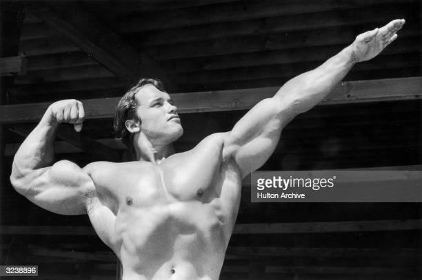 Austrian-born bodybuilder Arnold Schwarzenegger points one hand out as he flexes his torso on Muscle Beach, Santa Monica, California.