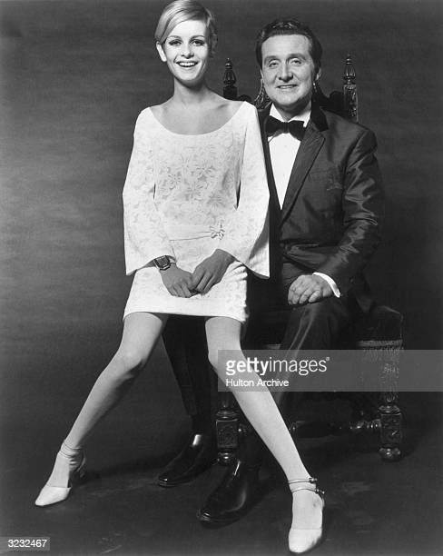 Full-length studio portrait of British model Twiggy laughing while sitting on the lap of British-born actor Patrick Macnee, who sits on a carved...