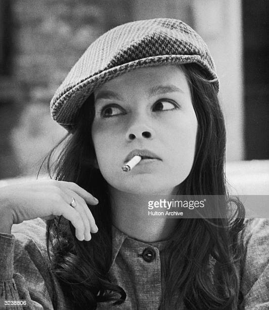 Headshot of FrenchCanadian actor Genevieve Bujold wearing a herringbone cap smoking a cigarette and looking to the side