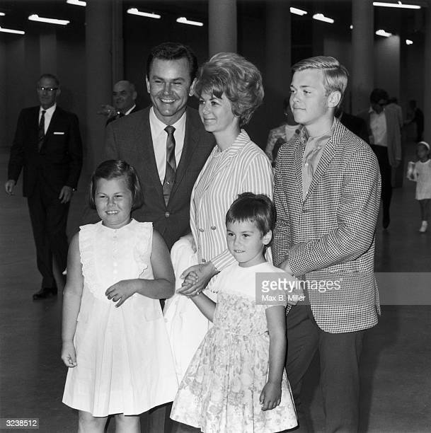 Portrait of American actor and former disc jockey Bob Crane standing and smiling next to his wife Anne Terzian their son and two daughters at a...