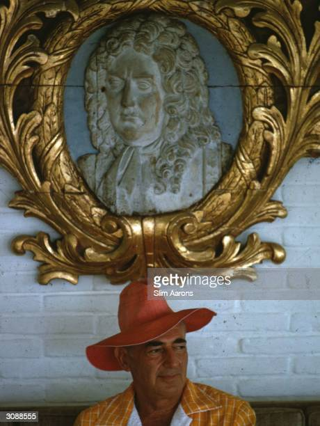 Wearing a sun hat in Acapulco Andrew Goodman above him a relief of Benjamin Franklin A Wonderful Time Slim Aarons