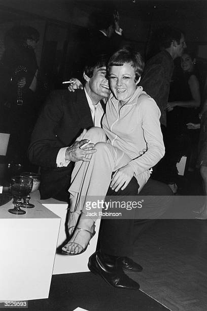 A woman laughs while sitting in her boyfriend's lap near the dance floor at the club Yellowfingers New York City Both smoke cigarettes