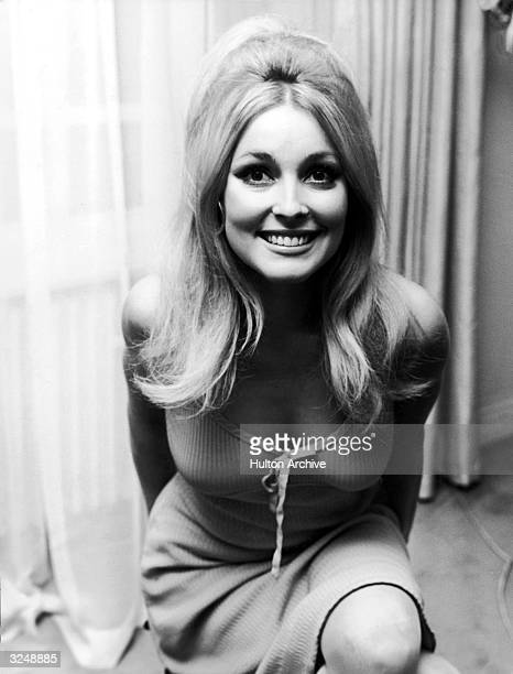 American actor Sharon Tate smiling in front of a window.