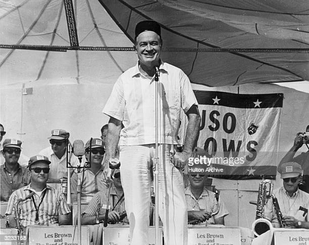 American entertainer Bob Hope standing on stage and smiling, with Les Brown's band, during a USO show to entertain American troops overseas, Vietnam...