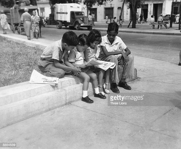 Children reading their comic books on a streetcorner in Cuba