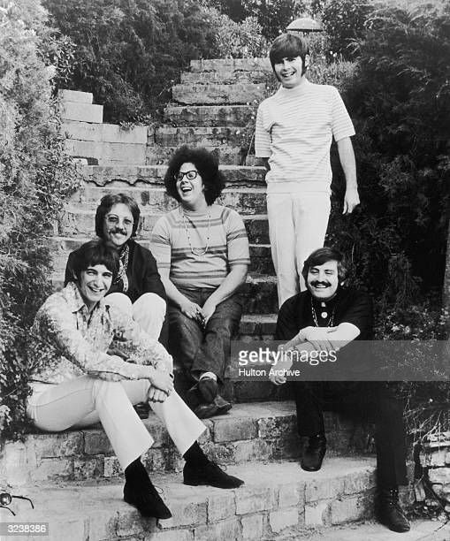 Portrait of pop group The Turtles sitting on the steps of a garden Members include Mark Volman and Howard Kaylan