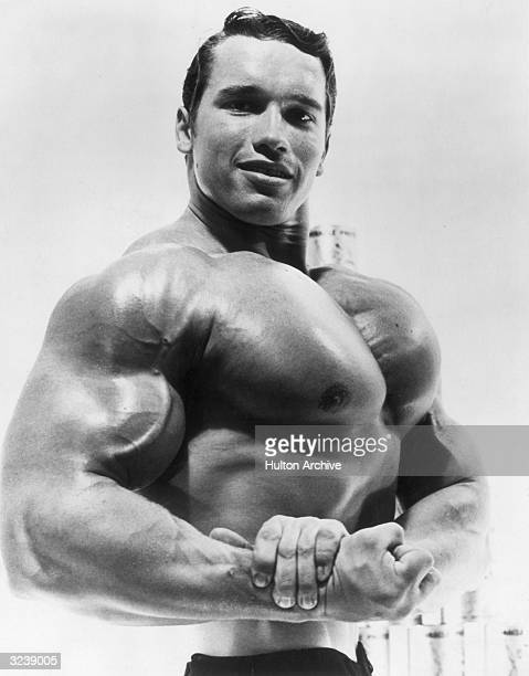 Studio portrait of Austrianborn bodybuilder Arnold Schwarzenegger flexing his torso in an advertisement for a German protein product