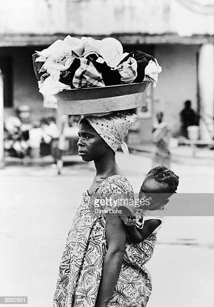 A Ghanaian mother carrying her child on her back in a traditional manner while balancing laundry on her head