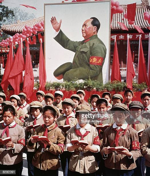 Group of Chinese children in uniform in front of a picture of Chairman Mao Zedong holding Mao's 'Little Red Book' during China's Cultural Revolution.