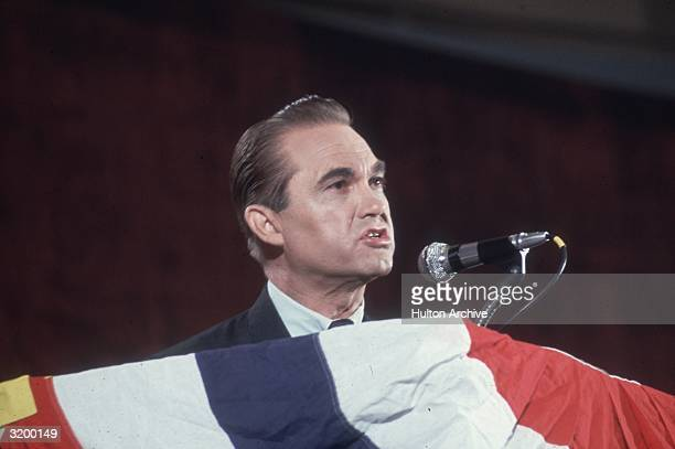 Alabama Governor George Wallace speaks into a microphone at a podium covered with a red white and blue banner late 1960s