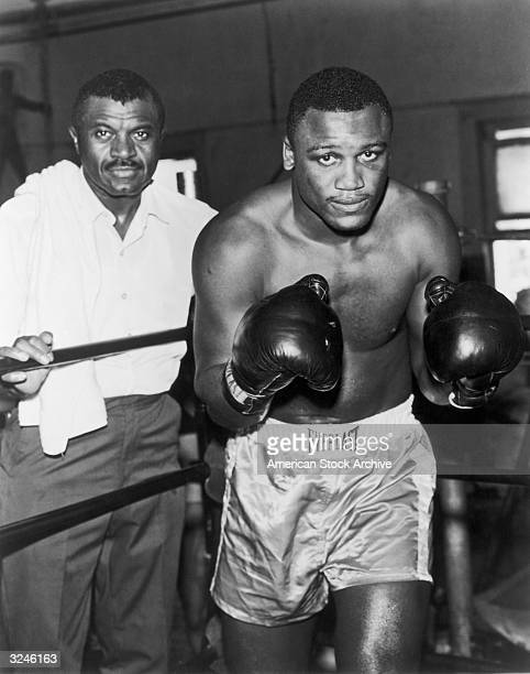 American heavyweight boxer Joe Frazier poses in a fighting stance in the ring with his trainer Eddie Futch behind the ropes