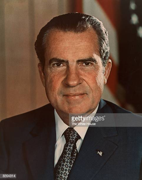 Headshot portrait of 37th American president Richard M Nixon wearing a US flag lapel pin smiling in front of a US flag Nixon's presidency lasted from...