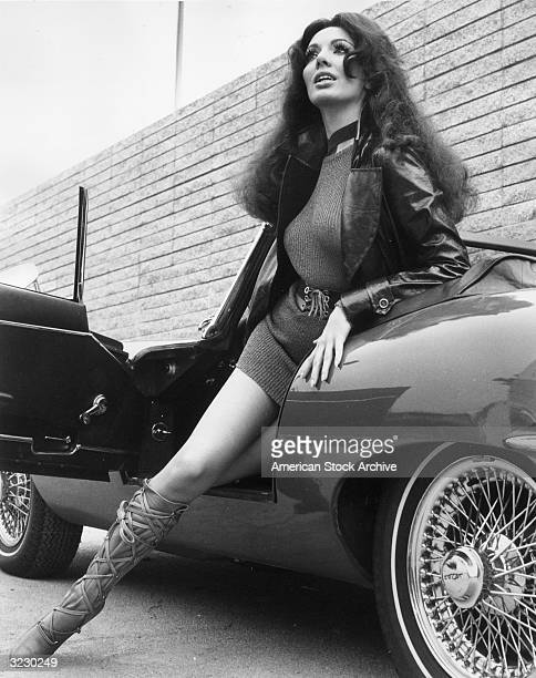 Low angle image of a woman stepping out of an EType Jaguar convertible sportscar wearing a leather jacket a minidress and laced cowhide boots
