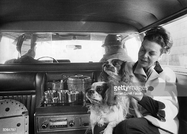 Metropolitan Opera director Dessen holds two rare Cavalier King Charles Spaniels in the back of a limousine on their way to the Met where the dogs...