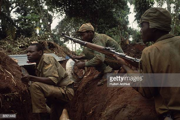 Nigerian men wear camouflage and hold their rifles as they move through the wilderness during Nigeria's Biafran civil war Members of the Ibo tribe...