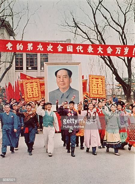 People marching down the street carrying a large poster of Chairman Mao Zedong during the Cultural Revolution, China.
