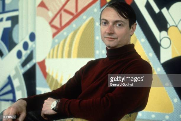 Portrait of American artist Roy Lichtenstein seated before one of his works