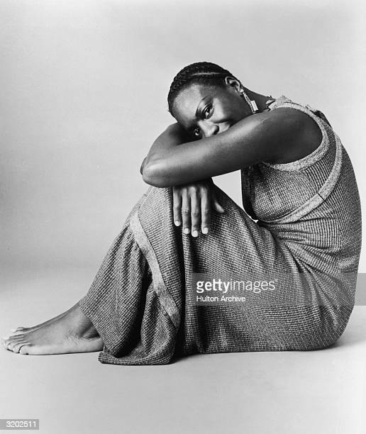 Studio portrait of American pianist and jazz singer Nina Simone resting her head on her arms while leaning on her knees