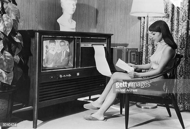 A Japanese woman sits on a living room set reading a faxed printout of the day's news from the television during a demonstration in Tokyo Japan