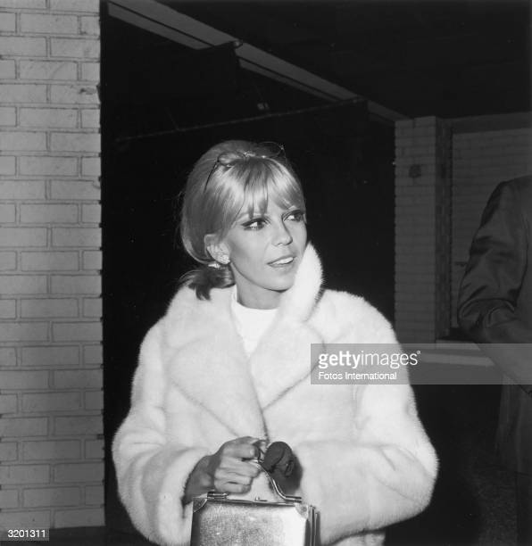 American singer Nancy Sinatra holds a box bag while wearing a lightcolored fur coat Sinatra has blonde hair and wears dramatic eye makeup including...