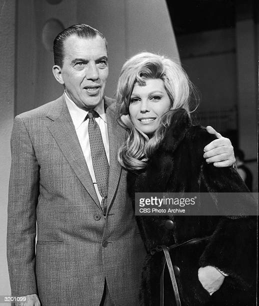 American TV host Ed Sullivan stands with his arm around singer Nancy Sinatra on stage, probably on 'The Ed Sullivan Show'. Sinatra has blonde hair...