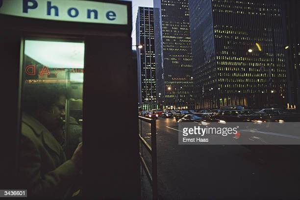 A caller uses a phone box on 6th Avenue New York as darkness begins to fall