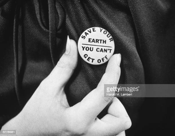 A closeup of a hand holding up an Earth day button which reads 'Save your Earth You can't get off'