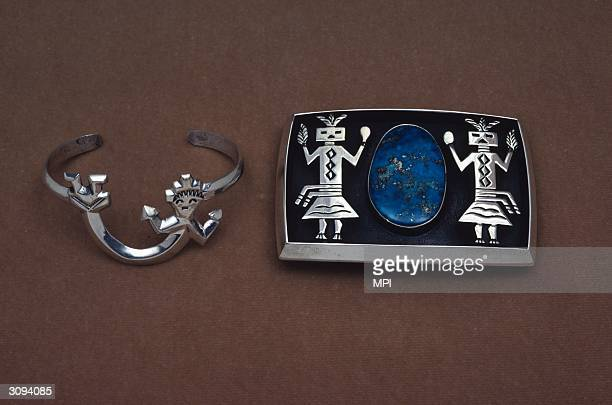 A closeup of a silver bracelet in the shape of the Navajo rainbow god and a silver buckle decorated with two Navajo Yeibichai dancers Both pieces...