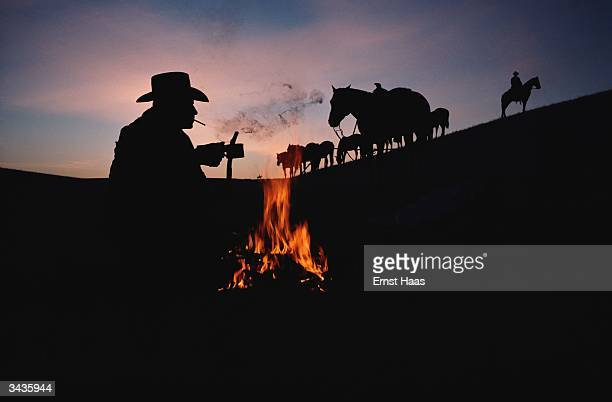 A cowboy sitting next to a camp fire in New Mexico In America book