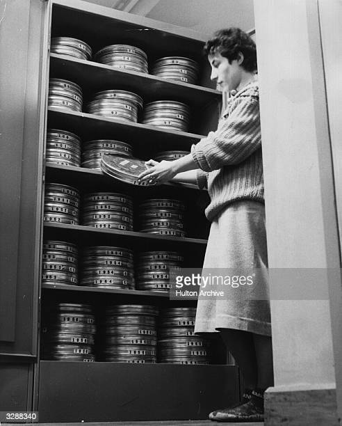 A grader at the British Museum Newspaper Library storing freshly processed negative film after being printed which is a great saving of space as...