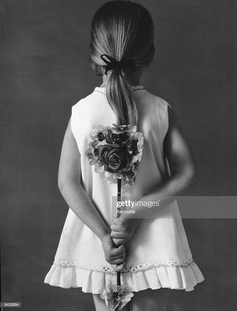 A little French girl holds a mirror bouquet behind her back., a gift for her mother on Mother's Day. The bouquet has a mirror on one side and on the other a large silk flower.