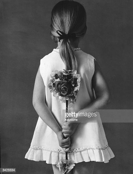 A little French girl holds a mirror bouquet behind her back a gift for her mother on Mother's Day The bouquet has a mirror on one side and on the...