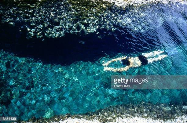 A man swims just below the surface of clear shallow water in Rhodes