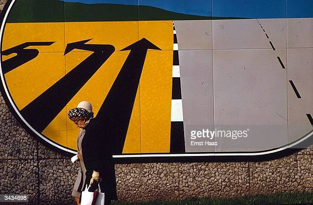 A woman walks past a design on a wall which looks like road markings stretching to a horizon