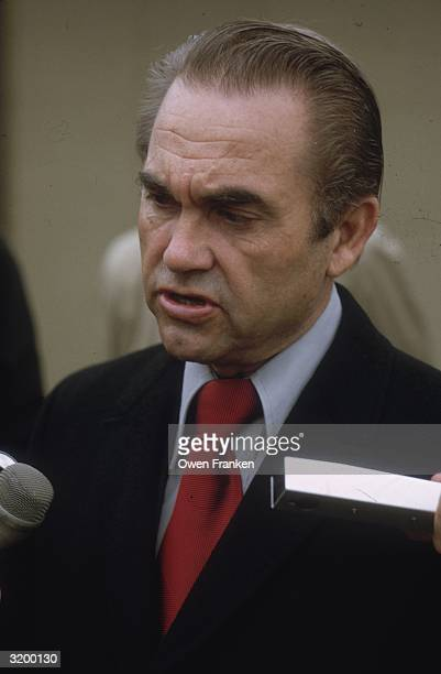 Alabama Governor George Wallace speaks to reporters wearing a red tie