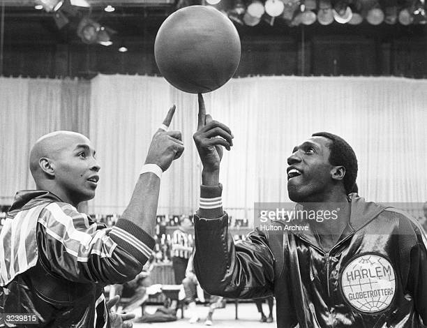 American basketball players Freddie Neal and Meadowlark Lemon of the Harlem Globetrotters pass a spinning basketball back and forth on their fingers